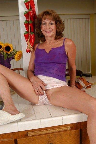 Old amateur granny posing in the kitchen