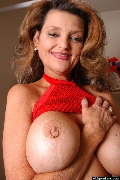 Older blonde woman Raven posing seductively in mesh bra and panties
