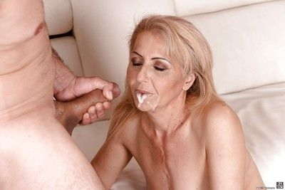 Blonde cougar Ilona G displaying hairy bush while sucking large penis