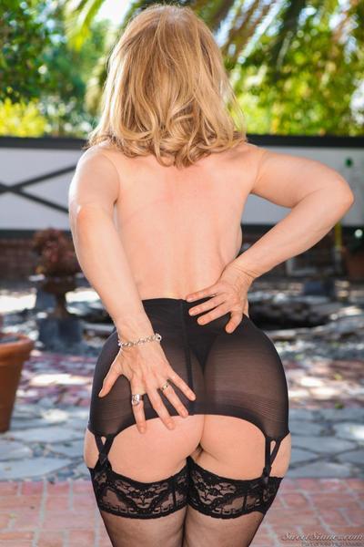 The blonde milf in erotic black lingerie Nina Hartley is showing her big boobs outdoor