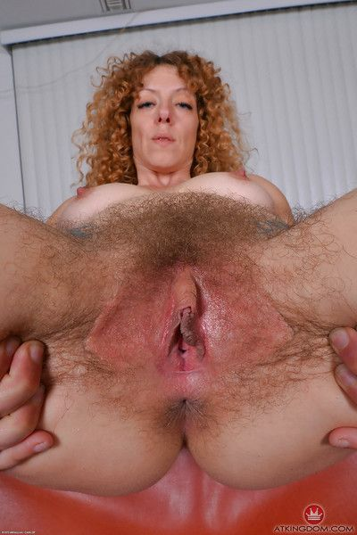 Older hirsute lady Leona spreading pink pussy for clitoral stimulation