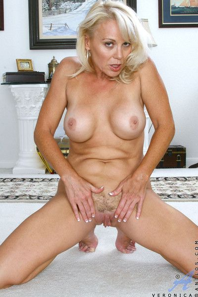Totally naked blonde milf loves to fondle her pink mature snatch while lying on