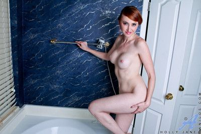 Sizzling redhead takes a masturbation break to test her glass dildo in the batht