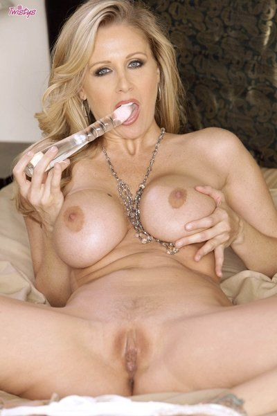 Bosomy Julia Ann strips out of her white lingerie and bangs her hole with glass dildo