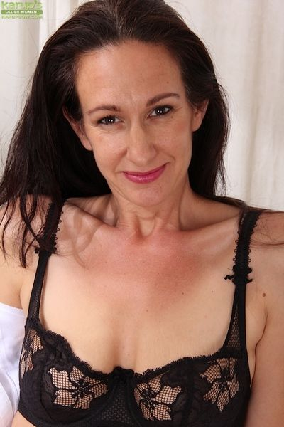 Dark haired mature babe Genevieve Crest showing her saggy tits