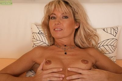 Older woman Janet Darling flashes her small tits and fingers pussy