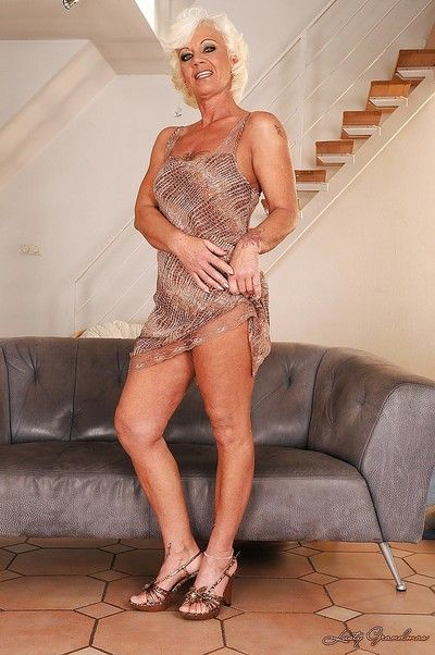 Lusty blonde granny on high heels stripping off her fancy dress