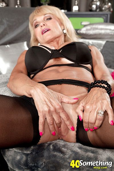 Older solo model Cara Reid stripping down to crotchless nylons to masturbate