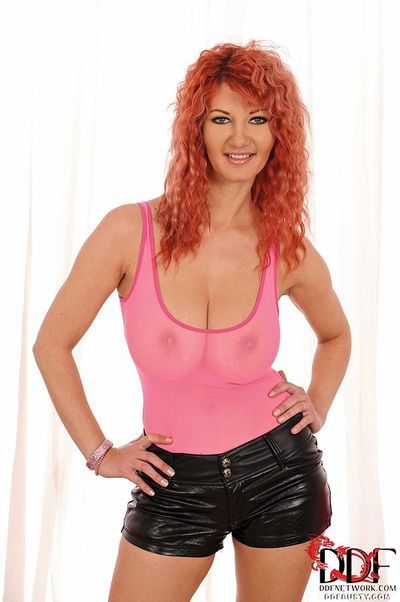 Busty redhead MILF Lovely Vanessa strips and shows off her voluptuous body