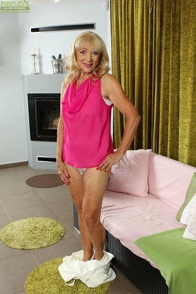 Ugly blonde granny Janet Lesley bares small saggy tits before masturbating
